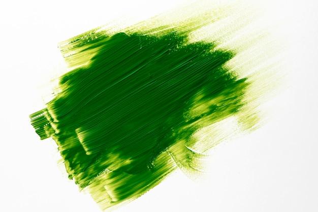 Zielony pociągnięcie pędzla na białym tle