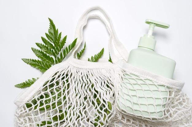 Zielony pojemnik na szampon, odżywkę lub mydło w płynie w ekologicznej torbie z zielonymi liśćmi. zero odpadów, koncepcja ekologicznych kosmetyków.
