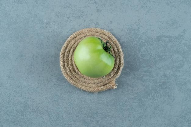 Zielony pomidor z liną na marmurze.