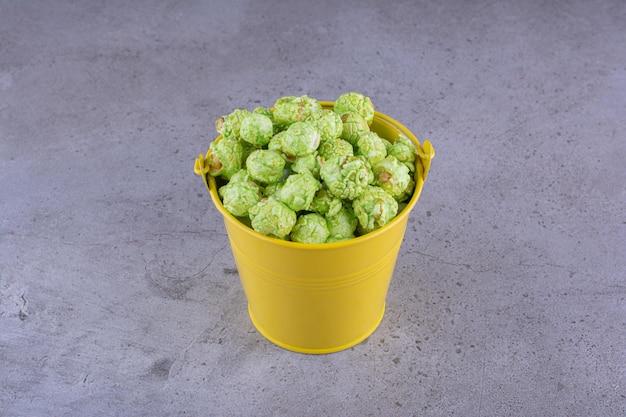 Zielony popcorn ułożony w żółte wiadro na marmurowym tle. zdjęcie wysokiej jakości