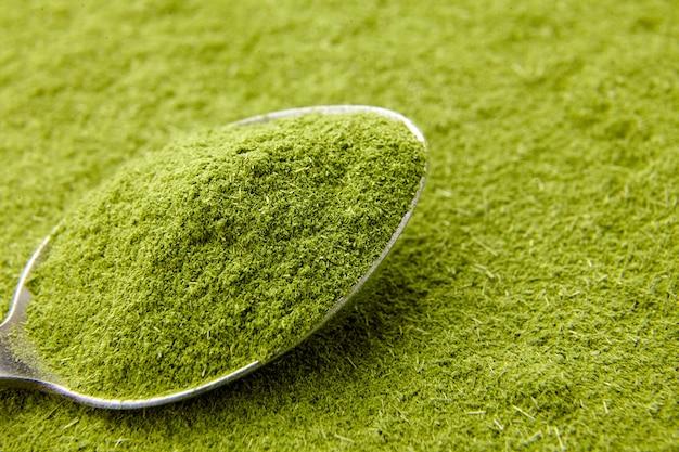 Zielony proszek z trawy pszenicznej w zbliżenie stalową łyżką