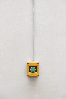 Zielony przycisk zainstalowany na urządzeniu typu push start lub stop na białym tle ściany