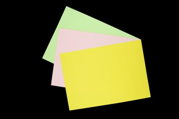 Zielony, różowy i żółty papier na białym tle na czarnym tle