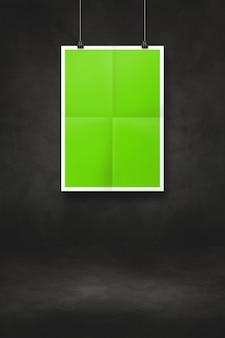 Zielony składany plakat wiszący na czarnej ścianie z klipsami. pusty szablon makiety