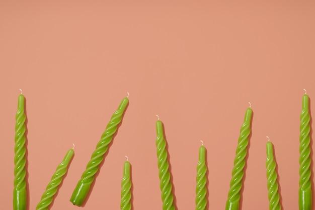 Zielony skręcony wzór świecy woskowej na jasnym pastelowym różowym tle układ partii kopiowanie miejsca