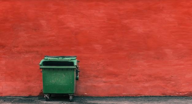 Zielony śmieciarski zbiornik na czerwonym ściennym tle