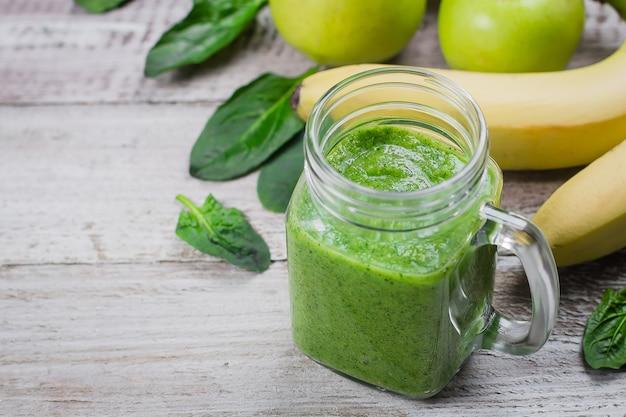 Zielony smoothie w słoiku z masonem z jabłkiem, bananem i szpinakiem