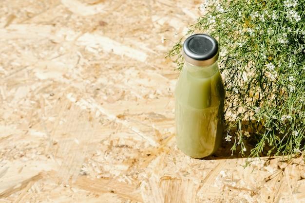 Zielony sok detoksykacyjny obok krzaka
