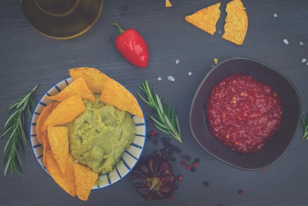 Zielony sos guacamole z chrupiącymi chipsami kukurydzianymi i sosem pieprzowym salsa w tonacji retro