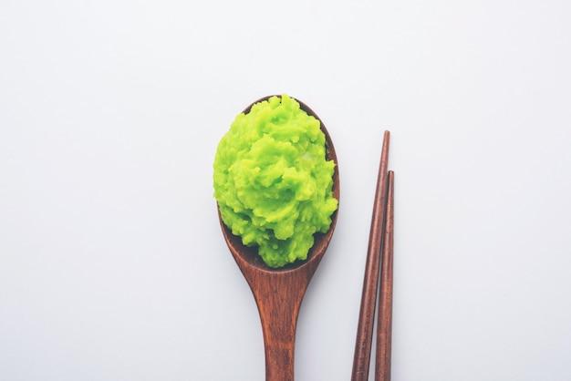 Zielony sos lub pasta wasabi w misce, pałeczkami lub łyżką na prostym kolorowym tle. selektywne skupienie