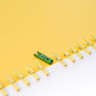 Zielony spinacz do bielizny otoczony żółtymi