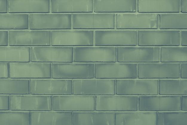 Zielony stary ściana z cegieł zakończenie z przeszyciami. tekstura kamiennego muru. ceglane tło dla fotografowanego obiektu leżącego płasko. koncepcja budowy i aranżacji wnętrz. skopiuj miejsce