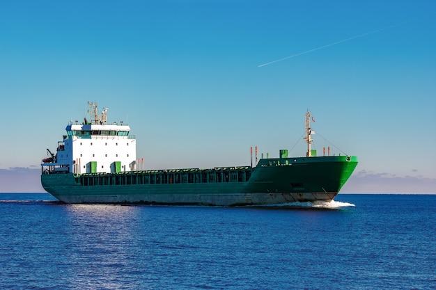 Zielony statek towarowy poruszający się w wodzie stojącej morza bałtyckiego