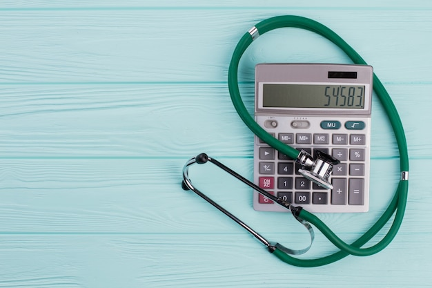 Zielony stetoskop w pobliżu kalkulatora na błękitnym drewnianym biurku. szary duży kalkulator.