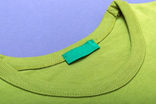 Zielony sweter z pustą etykietą na logo lub tekście.