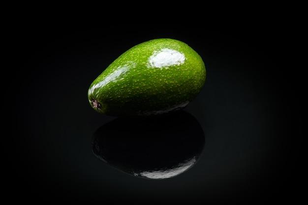 Zielony świeży awokado na czarnym tle z bliska