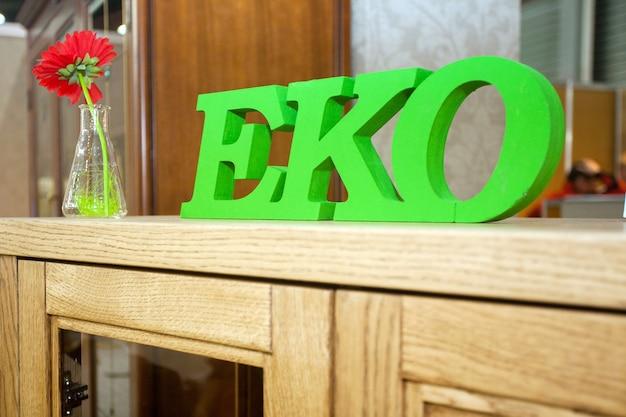 Zielony symbol tekstu ekologicznego na zbliżenie drewnianej komody