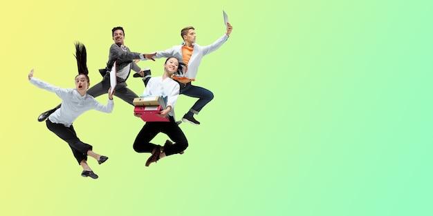 Zielony. szczęśliwi pracownicy biurowi skaczą i tańczą w zwykłych ubraniach lub garniturze na tle gradientowego płynu neonowego. biznes, start-up, praca w otwartej przestrzeni, ruch, koncepcja działania. kreatywny kolaż.