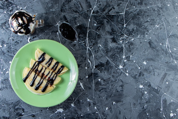Zielony talerz domowych naleśników z polewą czekoladową i szklanką mrożonej kawy.
