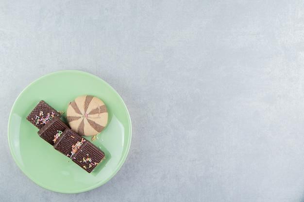 Zielony talerz pełen czekoladowych gofrów.