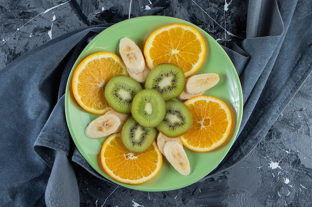 Zielony talerz pokrojony w plasterki pomarańczy, kiwi i banana na marmurowej powierzchni.