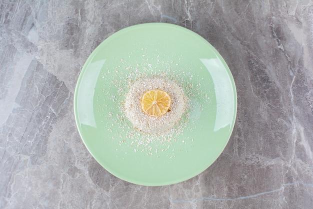 Zielony talerz pysznego jedzenia i plasterek świeżej cytryny .