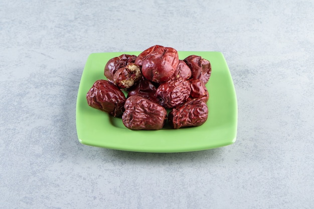 Zielony talerz smaczne dojrzałe srebrne jagody na marmurze.