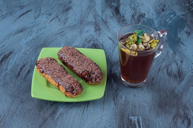 Zielony talerz z dwiema czekoladowymi eklerami i filiżanką herbaty na marmurowej powierzchni.