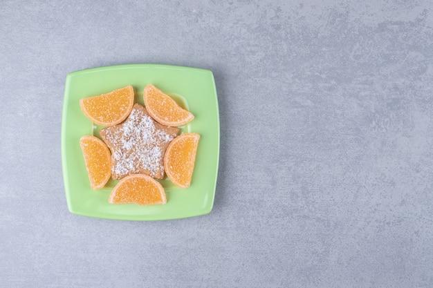 Zielony talerz z marmoladami i ciasteczkiem w kształcie gwiazdy na marmurowej powierzchni