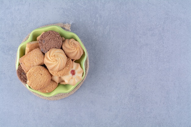 Zielony talerz ze słodkimi okrągłymi pysznymi ciasteczkami na worze.