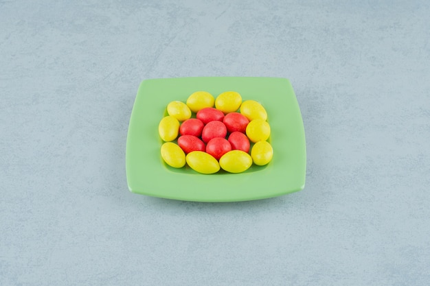 Zielony talerz ze słodkimi żółtymi i czerwonymi cukierkami na białej powierzchni