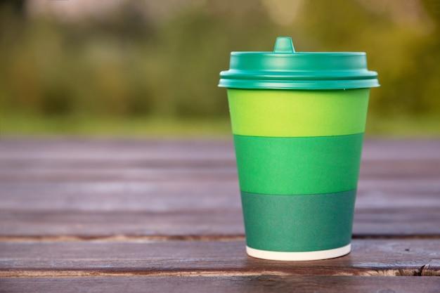 Zielony tekturowy kubek z plastikową pokrywką do kawy na drewnianym tle lub powierzchni, makieta, zbliżenie