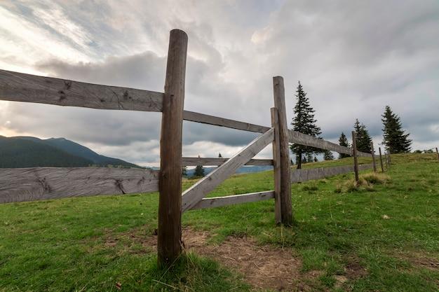 Zielony trawiasty dolinny stok z drewnianym ogrodzeniem i bramą na drzewiastej mgłowej górze pod błękitnym chmurnym niebem.