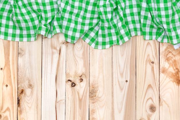 Zielony w kratkę obrus na drewnianym stole, odgórny widok