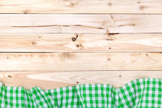 Zielony w kratkę obrus na drewnianym stołowym odgórnym widoku
