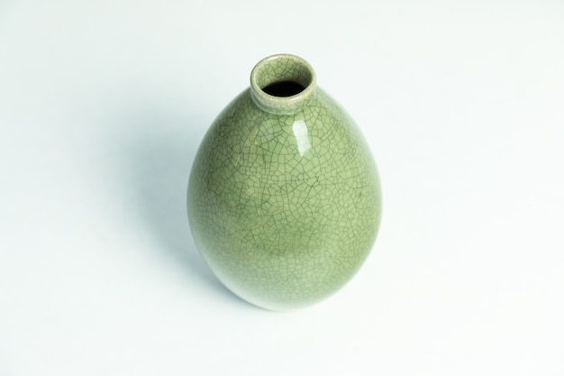 Zielony wazon ceramiczny na białym tle