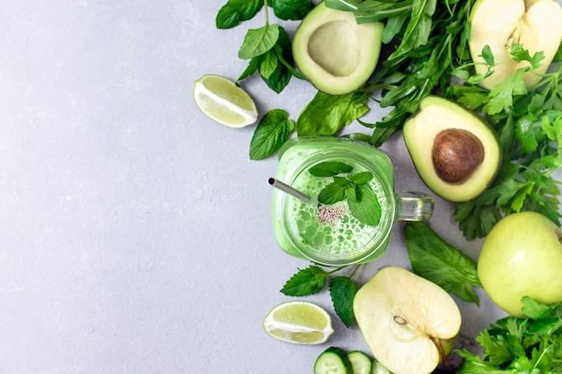 Zielony wegański koktajl wykonany z awokado, ogórka, jabłka, zieleni i limonki na betonowym tle