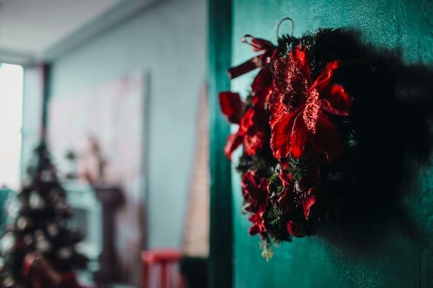 Zielony wianek ozdobiony czerwonymi kwiatami wisi na drzwiach