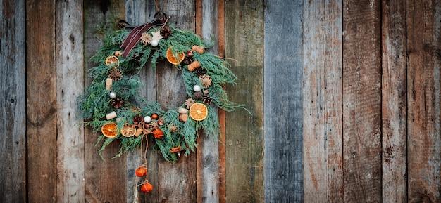Zielony wieniec bożonarodzeniowy na drewnianej ścianie, suszona pomarańcza, korek, jodła
