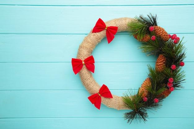 Zielony wieniec bożonarodzeniowy ozdobiony czerwoną kokardą na niebieskim tle drewnianych. święto dziękczynienia. widok z góry.