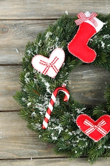 Zielony wieniec bożonarodzeniowy z dekoracjami na drewnianym tle