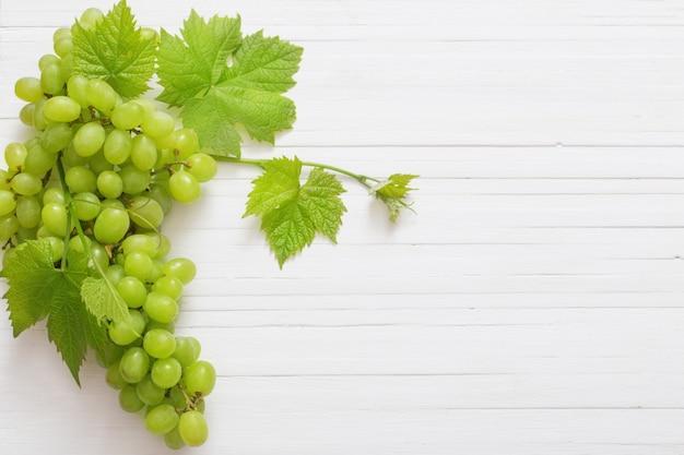 Zielony winogrono na białym drewnie