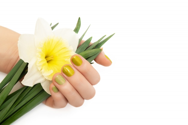 Zielony wzór paznokci. ręka z brokatem manicure trzyma kwiaty narcyzów.
