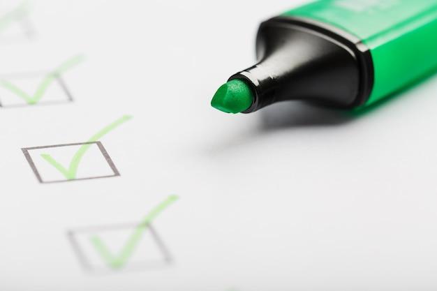 Zielony znacznik ze znacznikami na arkuszu listy kontrolnej. lista kontrolna zakończona koncepcja zadania.