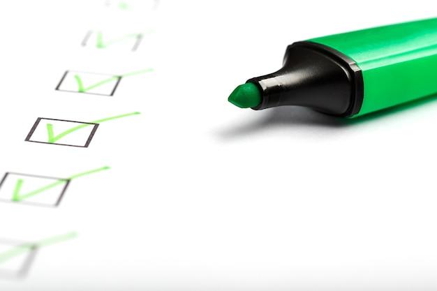 Zielony znacznik ze znacznikami na arkuszu listy kontrolnej