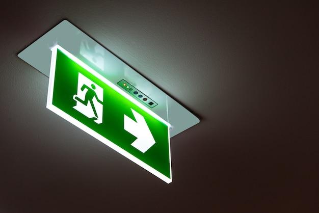Zielony znak wyjścia awaryjnego pokazujący sposób na ucieczkę.