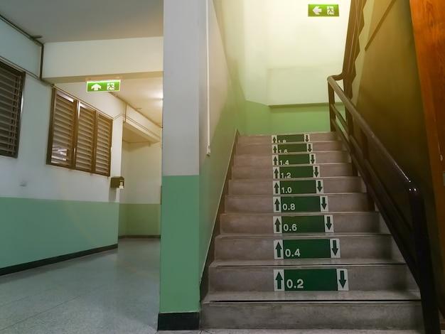 Zielony znak wyjścia ewakuacyjnego w szpitalu wskazujący drogę i schody do ucieczki