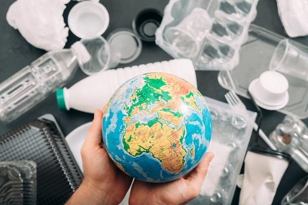 Ziemia utonęła w plastikowych śmieciach. zbliżenie kuli ziemskiej w ludzkich rękach. problem ekologii.