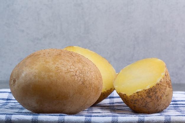 Ziemniak cały i pokrojony na marmurze.