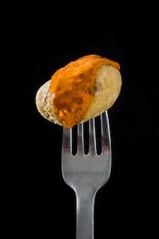 Ziemniak kanaryjski (papa arrugada) z sosem mojo na widelcu na czarno